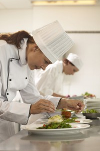 Female chef preparing plates of food, female cook in background