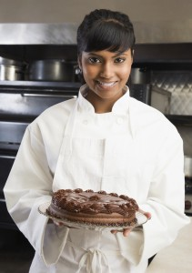 Female pastry chef holding cake